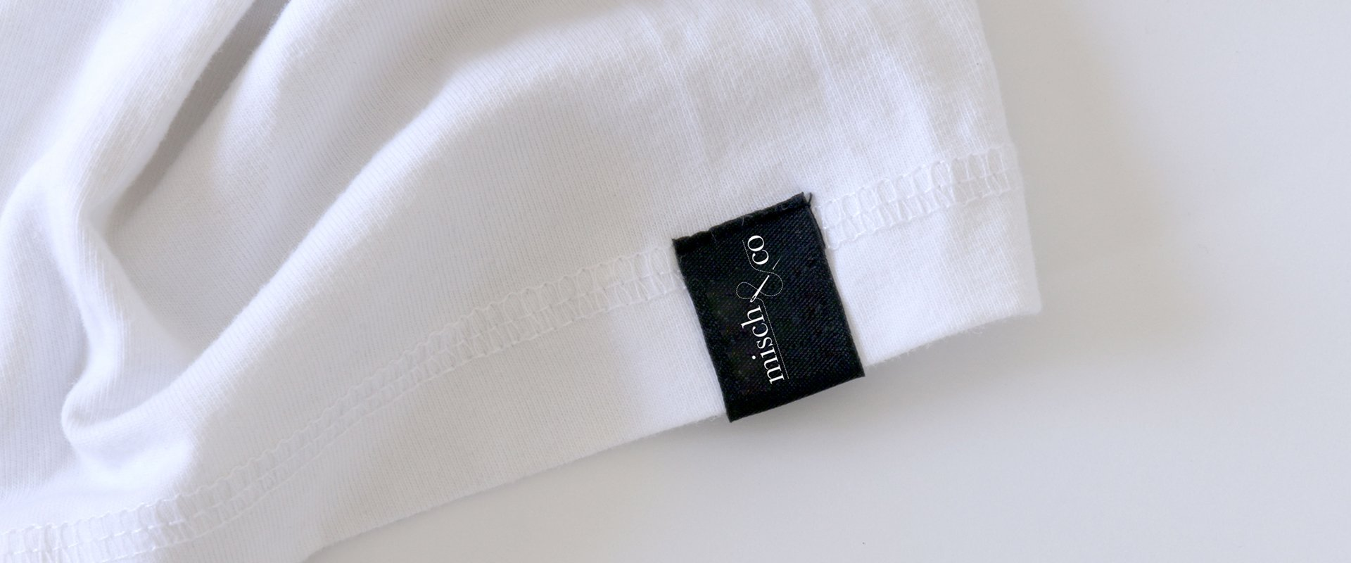 Branded t-shirt showing a small tag on the arm with company logo.